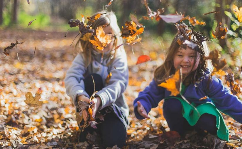 Young girls playing in a leaf pile