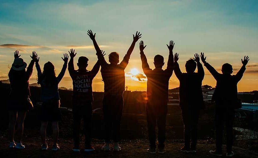Friends raising their hands in the air looking at the sunset together
